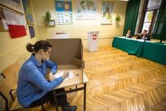 Kiezer bij de opiniepeilingspost tijdens poetsmiddel parlementaire verkiezingen aan zowel Sejm als Senaat Royalty-vrije Stock Foto