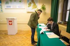 Kiezer bij de opiniepeilingspost tijdens poetsmiddel parlementaire verkiezingen aan zowel Sejm als Senaat Stock Afbeelding