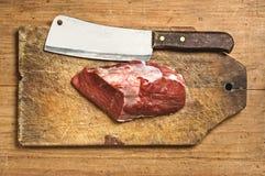 Kife do carniceiro e carne crua Fotos de Stock