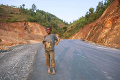 KIGALI, RWANDA - 6 DE SEPTIEMBRE DE 2015: Niño no identificado Un niño en la carretera de asfalto Imagenes de archivo