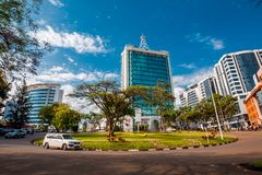 Kigali, Rwanda - September 21, 2018: A car passes the city centre roudabout, with Pension Plaza and surrounding buildings in. The background royalty free stock photo
