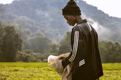 KIGALI, RWANDA - SEPTEMBER 6, 2015: Unidentified girl. The young laborer girl who gets ready to pick up tea plantations. Royalty Free Stock Images