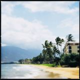 Kihei coastline. View of a sandy beach area and coastline with trees, buildings and a mountain under blue and cloudy skies in Kihei, Maui, Hawaii (USA Royalty Free Stock Photos