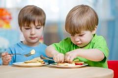 Kiids mangeant de la nourriture saine à la maison Photographie stock libre de droits