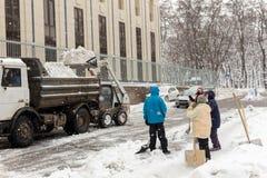 KIJÓW, UKRAINA - 21 GRUDZIEŃ, 2017: Pracownicy czyścą przejście przy budynku mieszkaniowego jardem podczas ciężkich opadów śniegu Zdjęcia Royalty Free
