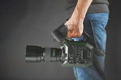 Kijów Ukraina, Kwiecień, - 22, 2018: kamerzysta trzyma jego fachowego kamera wideo Panasonic AU-EVA1 w studiu Obraz Stock