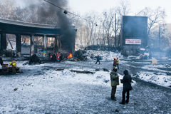 KIJÓW, UKRAINA: Mężczyzna w militarnych przekładnia strażnika barykadach na burnt ulicie w rząd ćwiartce podczas Euromaidan protes Obraz Royalty Free