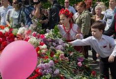 Kijów Ukraina, Maj, - 09, 2015: Dziecko kłaść kwiaty przy dziećmi kłaść kwiaty przy zabytkiem Fotografia Royalty Free