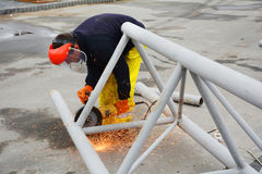 KIJÓW UKRAINA, MAJ, - 06, 2017: Pracownik używa elektrycznego ostrzarza metalu piłowanie z błysnąć iskrzy Pracownik ciie daleko k Zdjęcie Stock