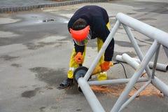 KIJÓW UKRAINA, MAJ, - 06, 2017: Pracownik używa elektrycznego ostrzarza metalu piłowanie z błysnąć iskrzy Pracownik ciie daleko k Obrazy Stock