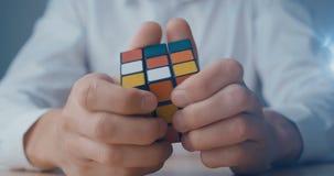 Kijów, Ukraina, Maj 07 2019: Zakończenie w górę biznesmena w koszula białych próbach rozwiązywać Rubik sześcian zbiory wideo