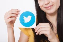 KIJÓW UKRAINA, SIERPIEŃ, - 22, 2016: Kobiet ręki trzyma świergotu logotypu icoi ptaka drukowali papier Świergot jest online Obrazy Stock
