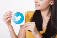 KIJÓW UKRAINA, SIERPIEŃ, - 22, 2016: Kobiet ręki trzyma świergotu logotypu icoi ptaka drukowali papier Świergot jest online Zdjęcia Stock