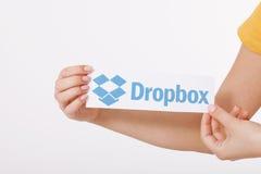 KIJÓW UKRAINA, Sierpień, - 22, 2016: Kobiet ręki trzyma Dropbox logotypu znaka drukujący na papierze na białym tle DropBox Obraz Royalty Free