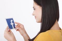 KIJÓW UKRAINA, Sierpień, - 22, 2016: Kobiet ręki trzyma facebook ikony znaka drukujący na papierze na białym tle Facebook Obraz Stock