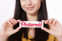 KIJÓW UKRAINA, SIERPIEŃ, - 22, 2016: Kobiet ręki trzyma Pinterest ilogotype przeciw drukowali papier Jest fotografii udzielenia s Fotografia Stock