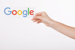 Kijów Ukraina, Sierpień, - 22, 2016: Kobieta wręcza trzymać Google logotyp drukuje na papierze na popielatym tle Google jest usa Obraz Royalty Free