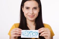 KIJÓW UKRAINA, Sierpień, - 22, 2016: Kobieta wręcza trzymać Skype logotyp drukuje na papierze na popielatym tle Skype jest a Zdjęcia Royalty Free