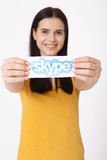 KIJÓW UKRAINA, Sierpień, - 22, 2016: Kobieta wręcza trzymać Skype logotyp drukuje na papierze na popielatym tle Skype jest a Obrazy Stock