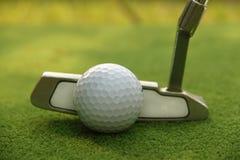 Kij golfowy i piłka golfowa zamknięci up w trawy polu z zmierzchem Gol Obraz Royalty Free