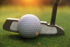 Kij golfowy i piłka golfowa zamknięci up w trawy polu z zmierzchem Gol Zdjęcia Royalty Free
