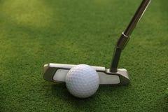 Kij golfowy i piłka golfowa zamknięci up w trawy polu z zmierzchem Gol Zdjęcie Royalty Free