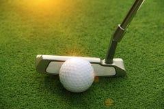 Kij golfowy i piłka golfowa zamknięci up w trawy polu z zmierzchem Gol Obrazy Royalty Free