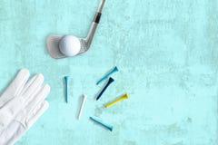 Kij golfowy, piłka golfowa i trójniki na zbudowanej powierzchni w turkusie, zdjęcie royalty free