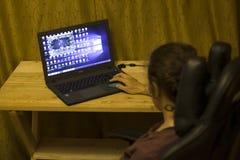 Kij?w, Ukraina 05 12 2019: dziewczyna bawi? si? online grzebaka dla laptopu Illustrative artyku?u wst?pnego zdjęcie stock
