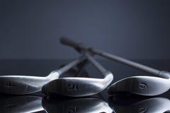 Kije golfowi kłama na zmroku - błękitna odbijająca powierzchnia Obrazy Stock