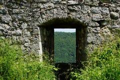 Kijk door de poort van de kasteelruïne aan bos stock afbeeldingen
