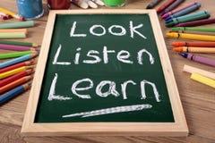 Kijk, luister, leer basisonderwijsconcept, schoolbank, bord royalty-vrije stock foto