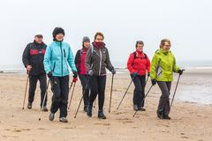 Senior female nordic walkers exercising on the beach. Kijkduin, The Hague, the Netherlands - 13 January 2018: nordic walkers on the beach Royalty Free Stock Images