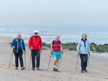 Group of senior nordic walkers on the beach. Kijkduin, The Hague, the Netherlands - May 12 2018: group of senior nordic walkers on the beach Stock Images