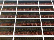 Kijkend in aanbouw upwards mening van de grote moderne commerciële bouw met staalstralen en balken met oranje veiligheidsomheinin stock afbeelding
