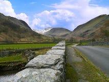 Kijkend onderaan weg, langs muur aan bergen Royalty-vrije Stock Afbeelding