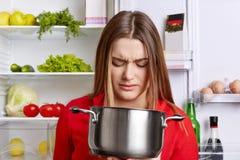 Kijkt de Angy niet bevallene vrouwelijke huisvrouw in pot met vuile maaltijd, sm stock foto's