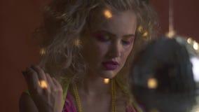 Kijkt de blonde jonge vrouw in retro kleren van achter de discobal, langzame motie stock videobeelden