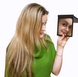 Kijkt in een spiegel Stock Fotografie