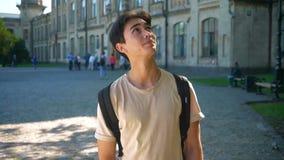 Kijkt het Aziatische mannetje van Nice omhooggaand en recht na, genietend de zomer van dagen, zijnd dichtbij grote oude gebouwen stock videobeelden