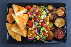 Kikärtsallad med aubergine, grönsaker och pitabrödet Arkivfoto
