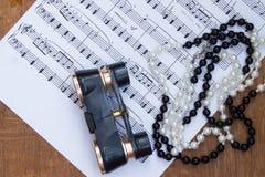 Kikare och halsband på bakgrund av musikanmärkningar Royaltyfri Foto