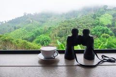 Kikare och kaffekopp på trä med suddig backgrou för skog Arkivbilder