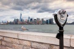 Kikaren på Ellis Island pekade in mot horisont I för Manhattan ` s Royaltyfri Fotografi