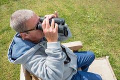 kikareutforskare som ser äldre hålla ögonen på för mannatur royaltyfria bilder