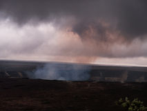 Kilauea volcano with smoke rising. Kilauea volcano with red smoke rising and joining the clouds. Hawaii Big Island Volcano National Park Royalty Free Stock Images
