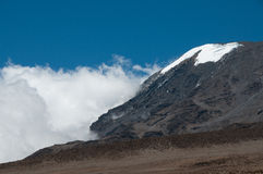 Kilimanjao in clouds. The glaciers of Kilimanjoro from the descent route from Kibo Huts. The trial to Stella point with walkers is visible to the right of the Royalty Free Stock Photography