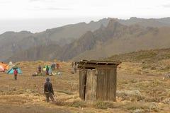 2014 02 Kilimanjaro, Tanzânia: O homem entrou no toalete de madeira imagem de stock