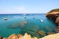 Kilka łodzie żeglują przez kryształu nawadniają blisko do pięknej wioski i plaży Sa Riera Fotografia Royalty Free