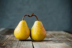 Kilka Świeże dojrzałe organicznie żółte bonkrety tworzą kształt serce na nieociosanym drewnianym stole na zmroku - szarości kamie Obrazy Royalty Free